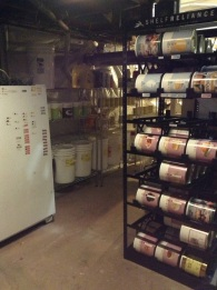 view of freezer and multiple shelving units filled with long term food storage cans and buckets