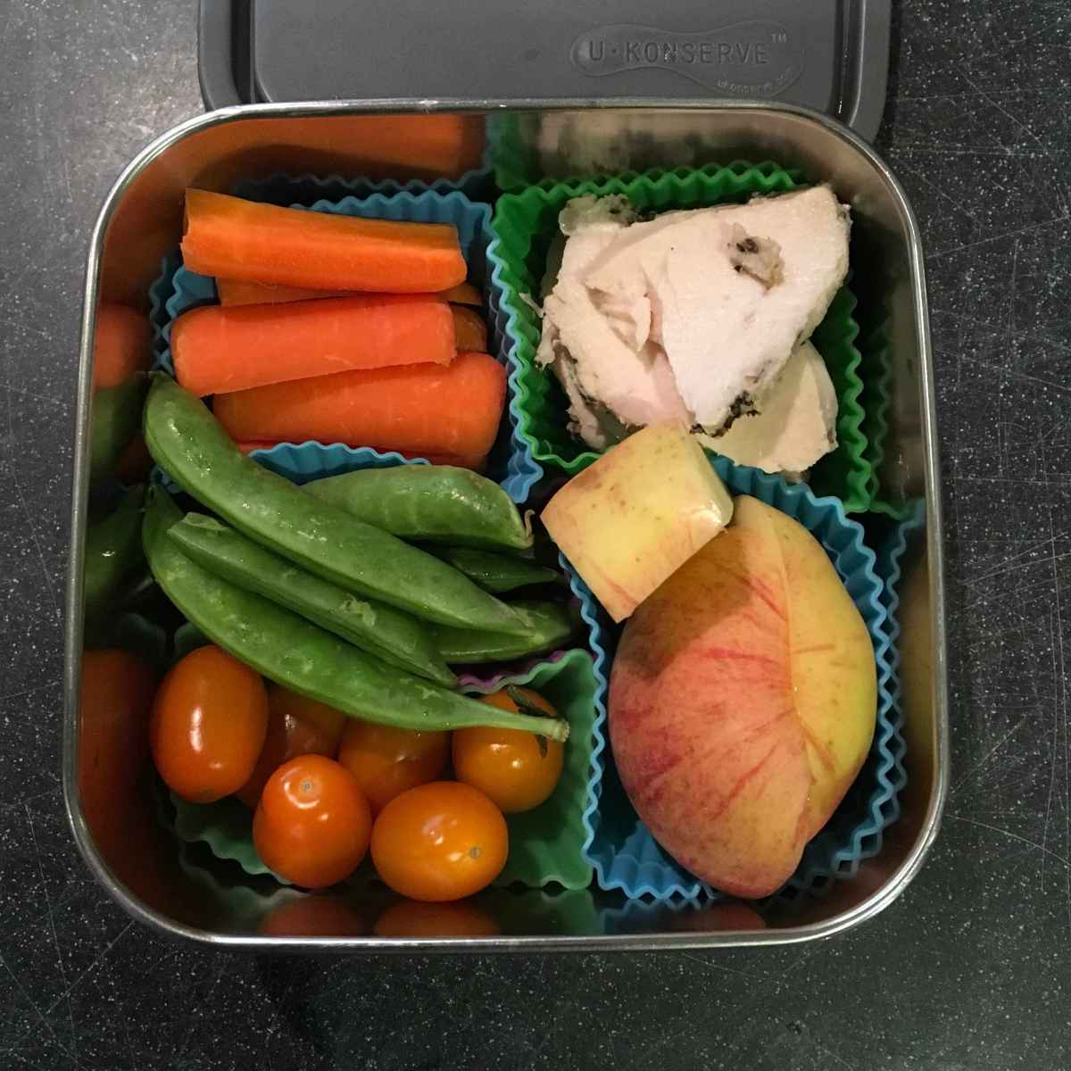 Veggies, fruit, and meat separated in U Konserve square steel dish using silicone cups