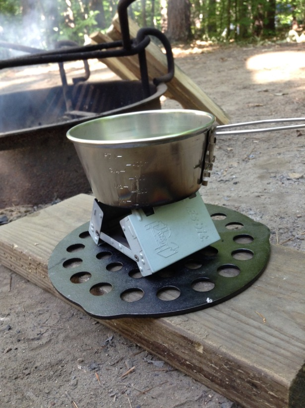 Tin cup heating over micro size solid fuel camping stove in front of fire pit