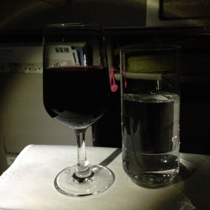 Glasses of wine and water on airplane tray table