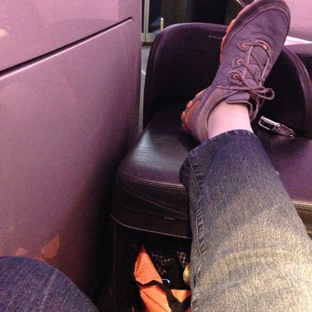 Foot resting on ottoman in Business Class plane cabin
