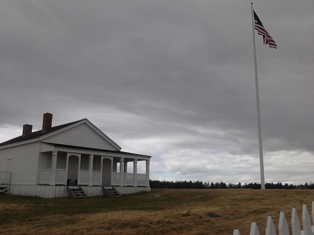 US flag flying against cloudy sky over old building
