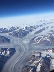 View of glaciers flowing past mountains from plane flying over Greenland
