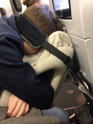Young man sleeping on plane leaning forward wiht face buried in inflatable pillow