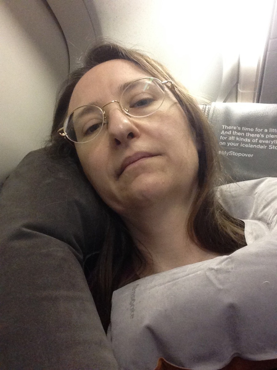 Airline passenger in Economy class with two inflatable pillows trying to sleep