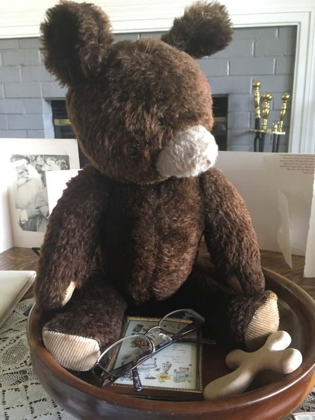 Memorial display: teddy bear, eyeglasses, cross, photo