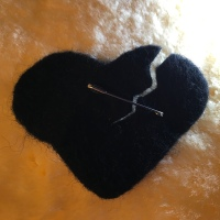 Torn black felt heart pinned to garment to signify grief and k'riah