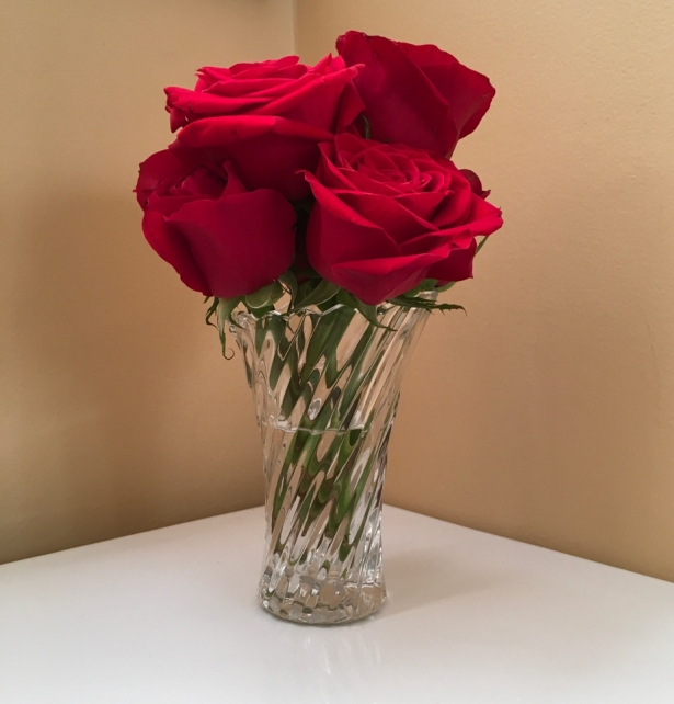 Half a dozen red roses in a small crystal vase