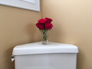 Small crystal vase of red roses atop white ceramic toilet tank