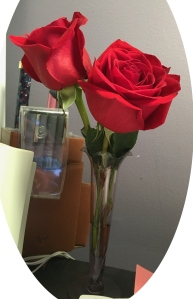 3 red roses in a short, tulip-shaped bus vase of purple glass