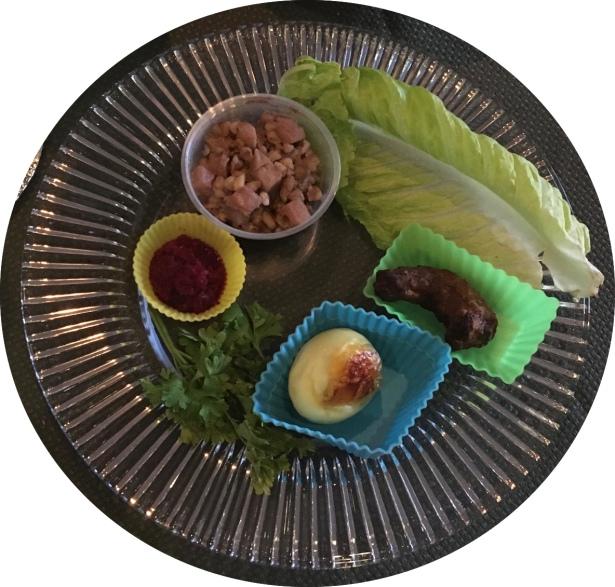 seder plate with bitter herbs, charoset, shank bone, etc.