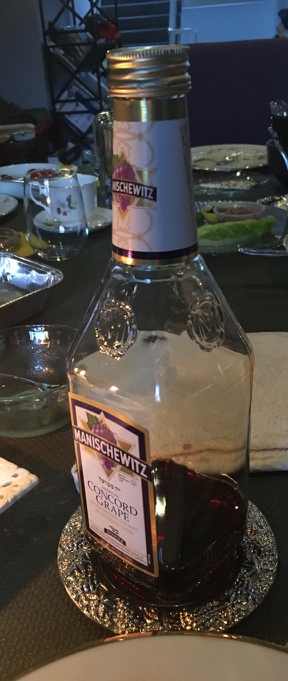 Manischewitz kosher wine bottle, mostly empty, on silver salver