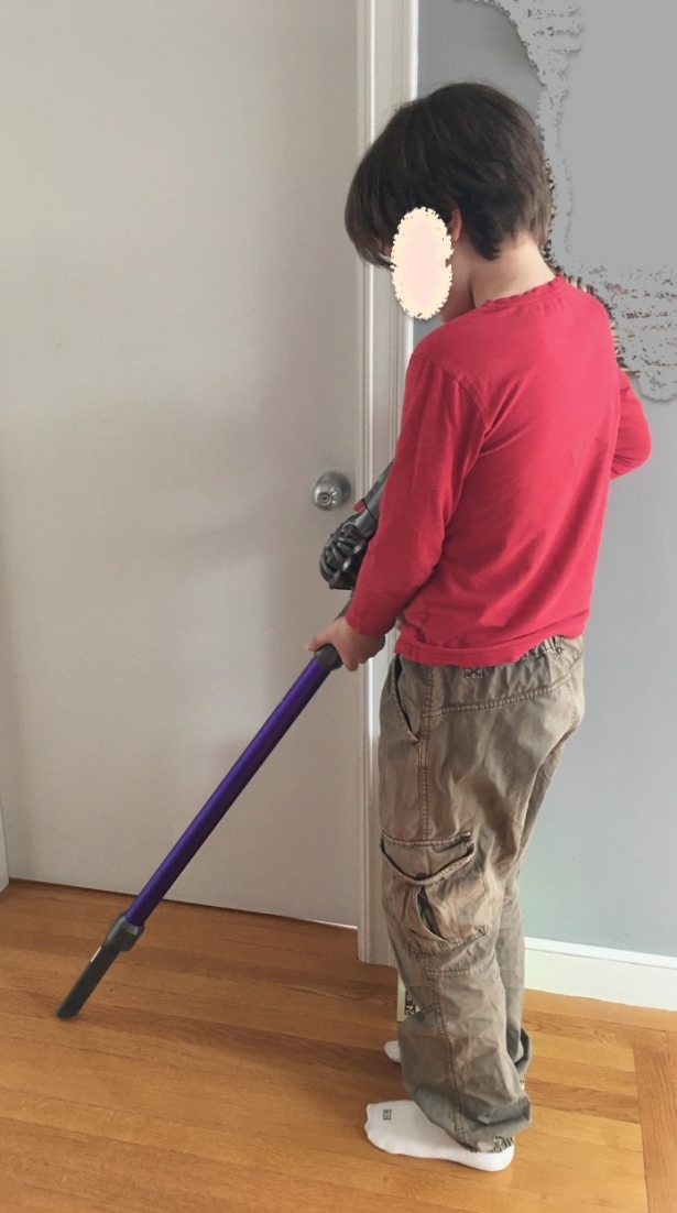 Boy holding stick vacuum as if cleaning the floor
