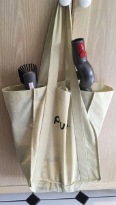 Vacuum accessories in old shopping bag hung from cabinet handle