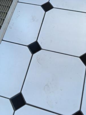 Muddy footprints on kitchen tile floor