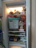 Side by side freezer whose open door shows mostly full shelves