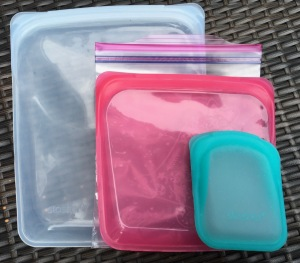 Large, medium & small Stasher silicone storage bags with quart size Ziploc bag to show size