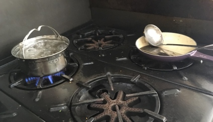 Saratoga Jack secondary cook pot boilding water on messy stove top next to used fry pan