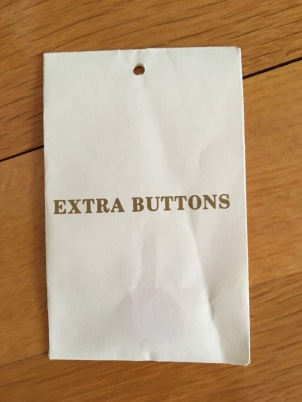 Paper envelope hang tag containing Extra Buttons