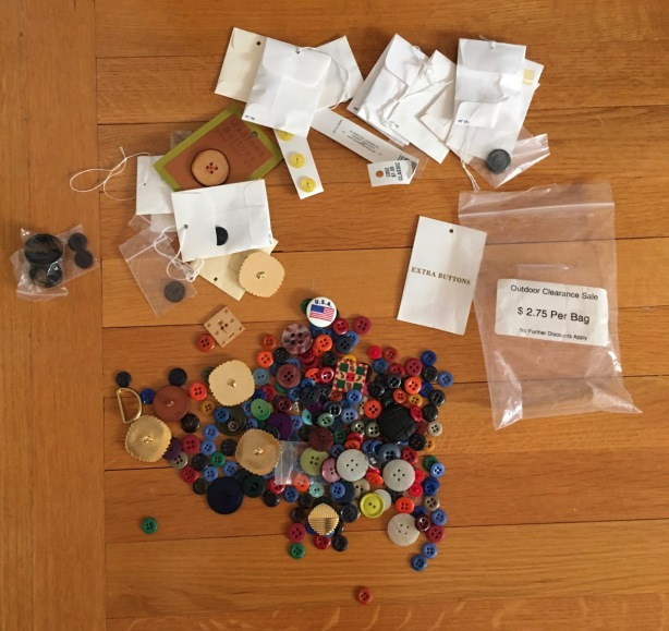 Dozens of buttons strewn across wood floor