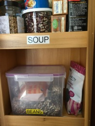 pantry shelf with half a dozen packages of various types of dried beans