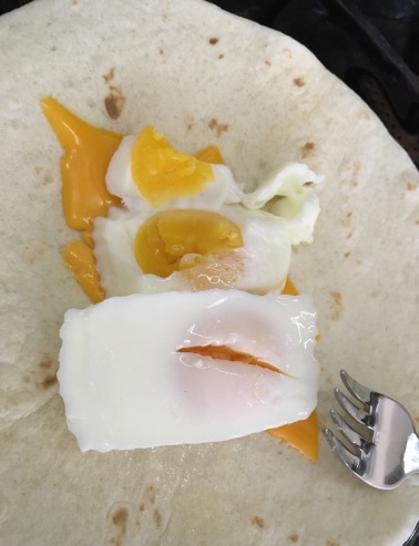 rectangular poached eggs on tortilla over melted cheese