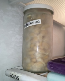 home cooked white beans in jar on freezer shelf