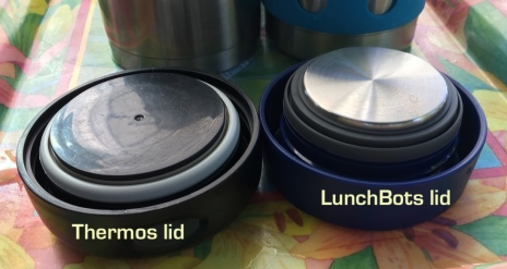 Black plastic Thermos lid next to blue plastic LunchBots lid whose interior is lined with stainless steel