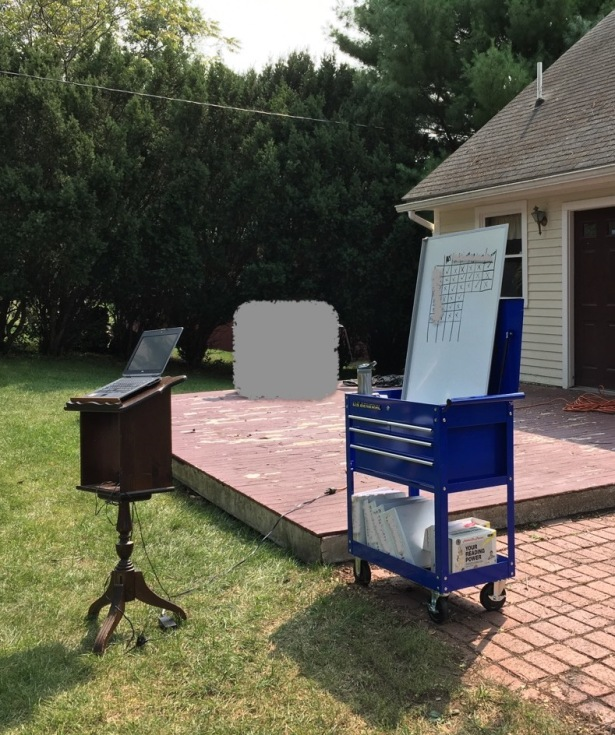 Lectern with laptop and whiteboard propped on mobile tool cart outside