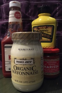 Condiment bottles: ketchup, mayo, mustard, harissa