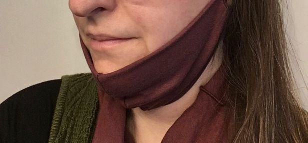 purple fabric mask pushed below the chin on woman's face