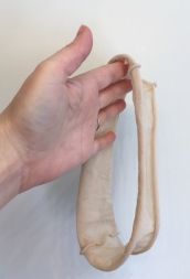 woman's hand holding tube of nylon cut from pantyhose
