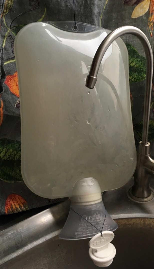 Fashy hot water bottle hanging upside down with cap off to drip dry over sink