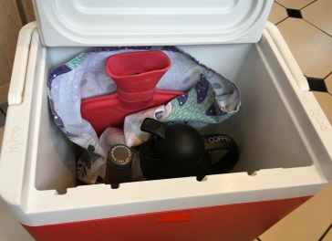 Cooler stocked with hot water bottle, coffee and wine for outdoor guests in cold weather