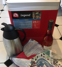 Red Igloo cooler with coffee carafe, bottle of wine, and red rubber hot water bottle wrapped in towel