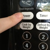pressing power level button on microwave control panel