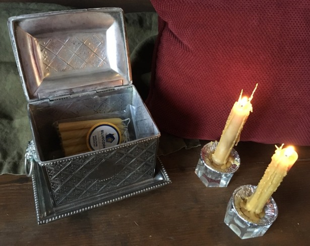 2 lit tapers on wooden table next to open silver chest containing beeswax candles
