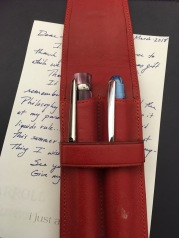 2 fountain pens in red leather sleeve atop hand scrawled note