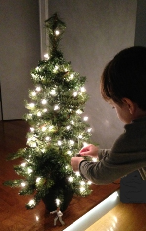 child hangs ornament on small Christmas tree