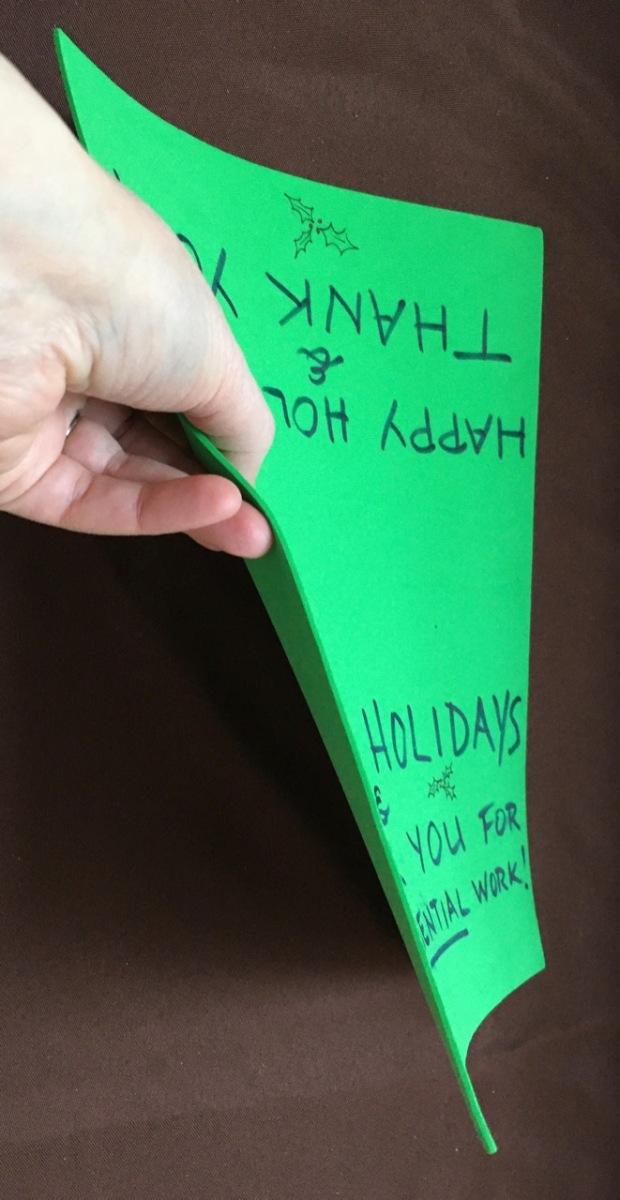 """hand demonstrating flexibile nature of green foam """"paper"""""""