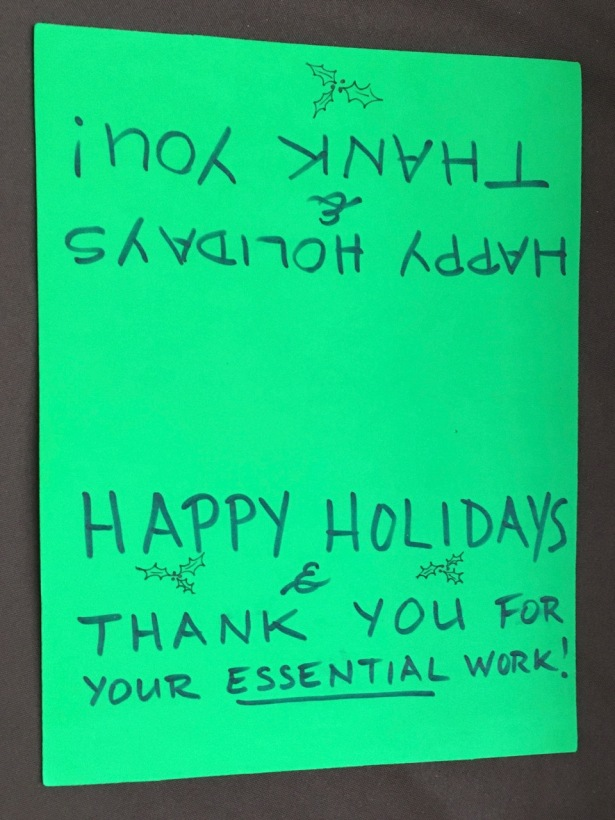 Green foam sheet saying Happy Holidays & Thank You to essential delivery workers