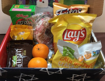 Close up of snacks: Apple Jacks cereal, M&M candy, tangerines, doughnut, chips, crackers