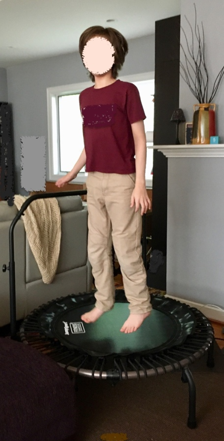 child jumping on mini trampoline in living room