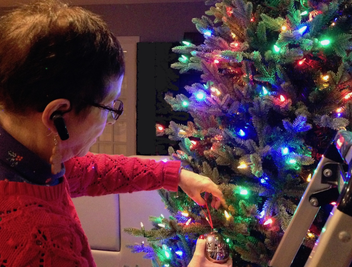 Mom decorates Christmas tree with ornament
