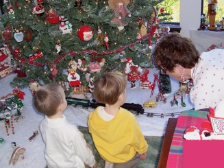 Mom runs antique toy train under Christmas tree for toddler kids