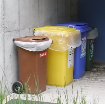 brown compost bin, yellow trash barrel, and blue and green recycling bins for curbside collection
