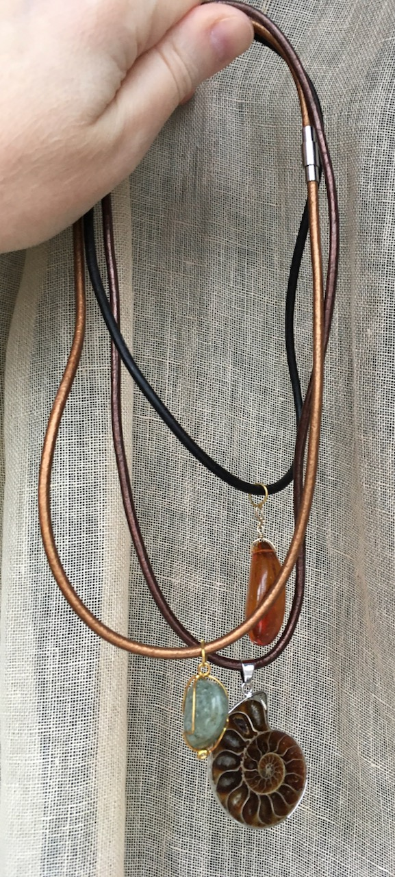 Pendant necklaces: amber bead on black cord, ammonite fossil pendant on brown cord, blue stone on bronze cord
