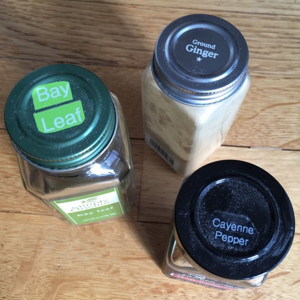 Spice jar tops with raised ring on green Simply Organic lid, silver Whole Pantry lid, and black plastic Trader Joe's lid