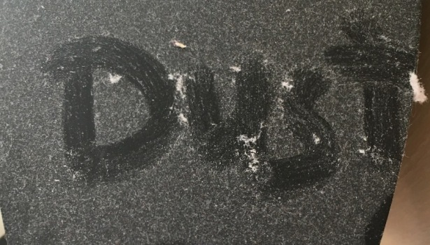 "The word ""dust"" scraped onto a dusty black surface"