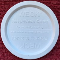 Weck canning jar lid in plastic, top view, reminds user not to use freshness cover for canning